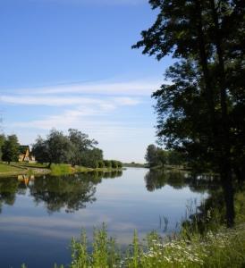 Veekogu, sinist taevast peegeldav järv, kaldal puud ja maja.